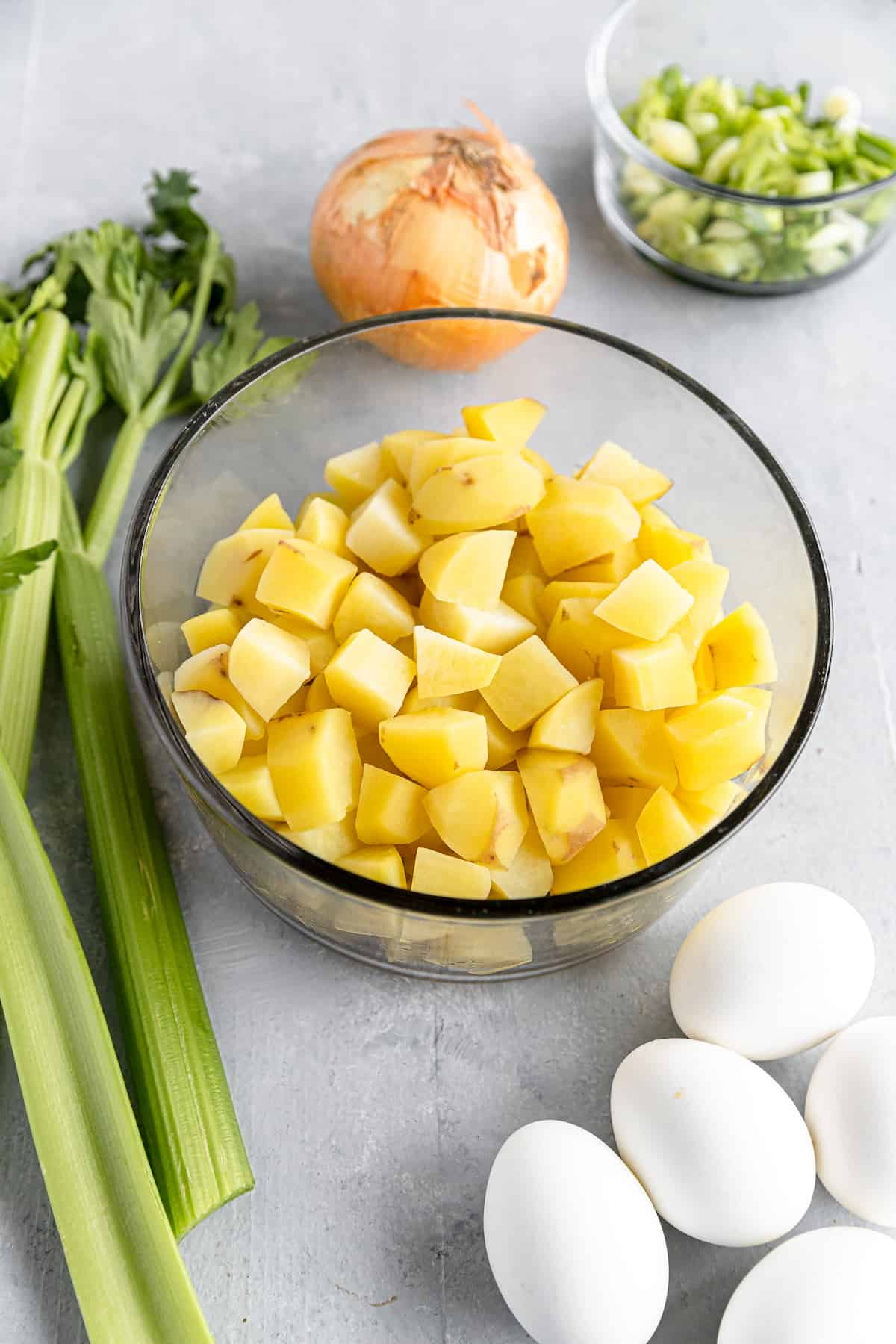 Chopped Potatoes, Hard-Boiled Eggs, a Yellow Onion and the Rest of the Potato Salad Ingredients on a Gray Countertop