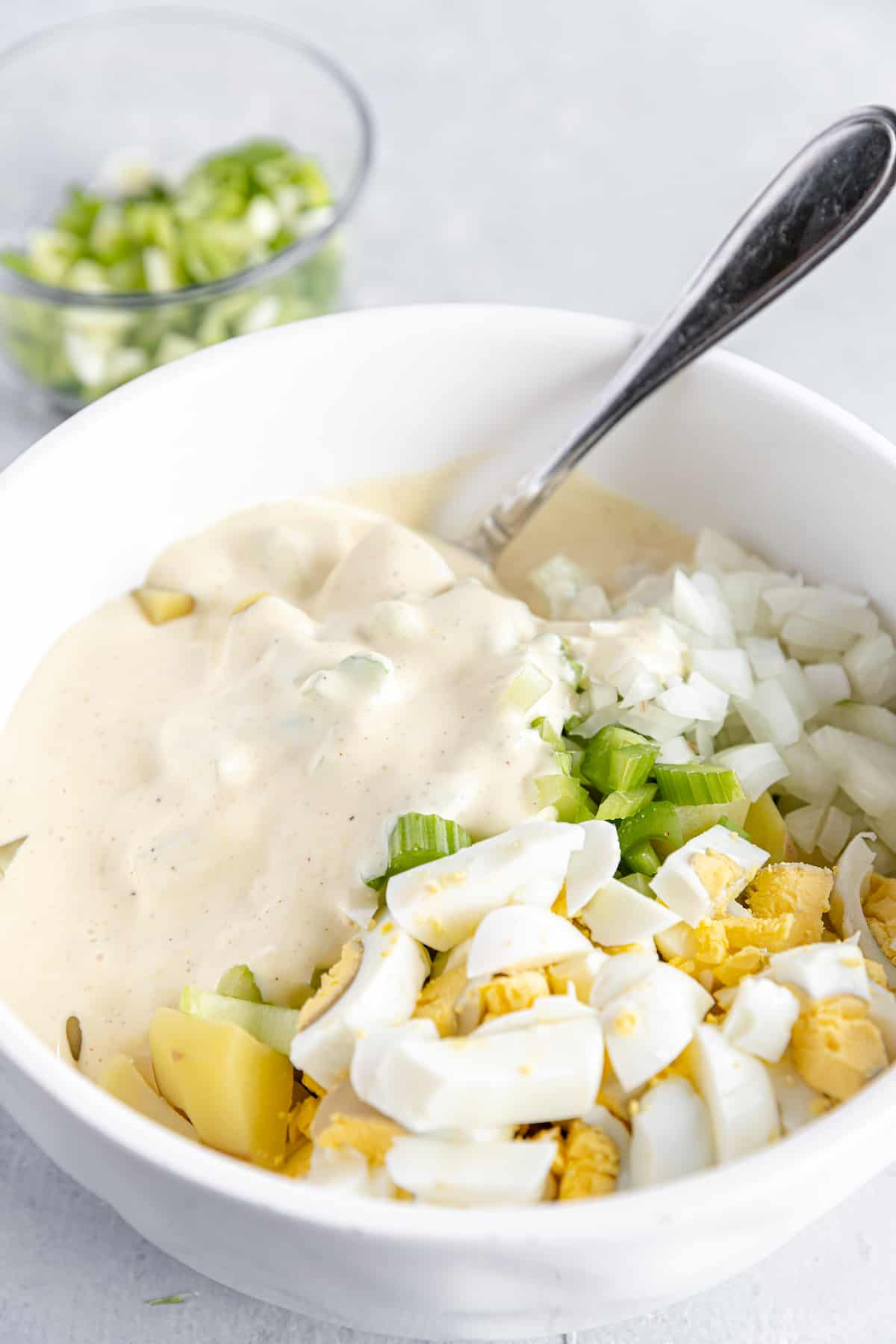 Mayonnaise Dressing Added Into the Bowl of Unmixed Potato Salad Ingredients