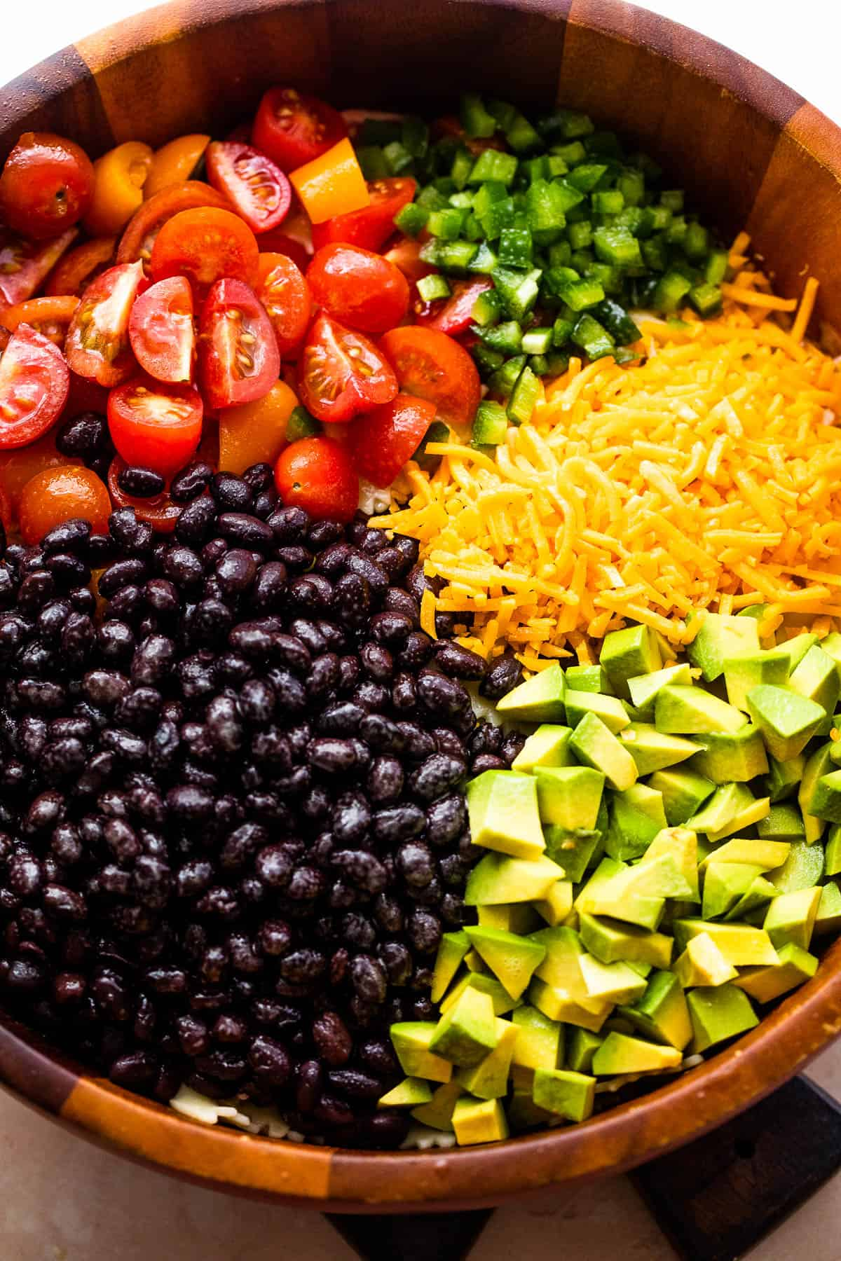 wooden bowl with chopped up tomatoes, avocado, shredded cheese, and black beans
