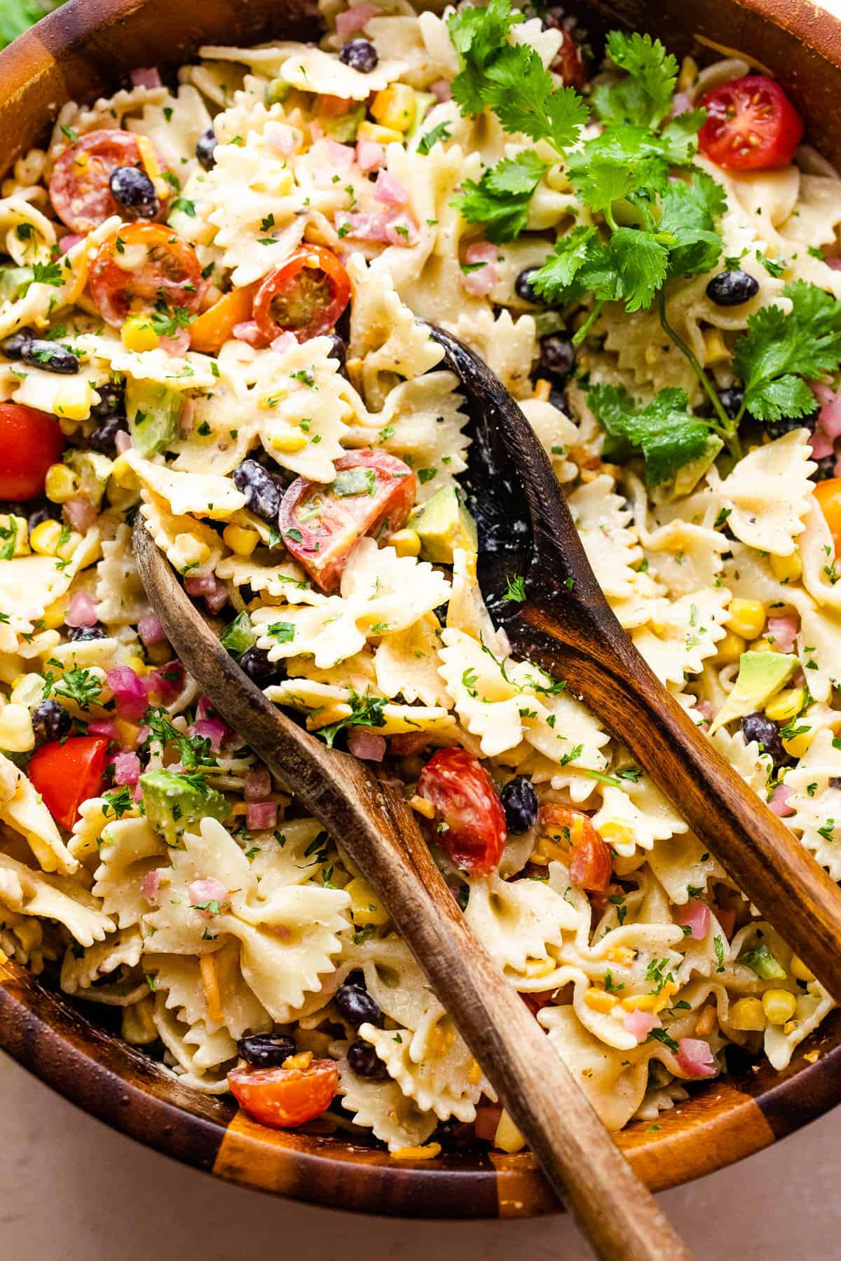 pasta salad in a wooden salad bowl with two wooden spoons