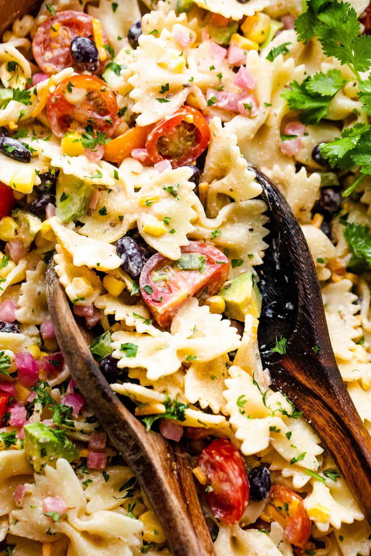 up close shot of fiesta pasta salad in a wooden salad bowl with two wooden spoons