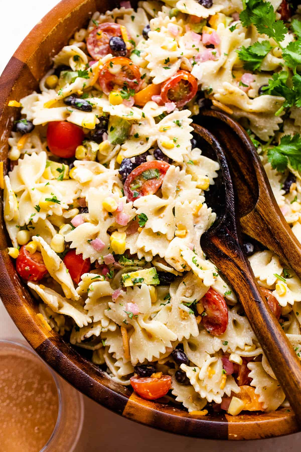 fiesta pasta salad in a wooden salad bowl with two wooden spoons