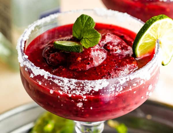 Frozen Berry Margarita served in a margarita glass with salted rims, slice of lime, and mint
