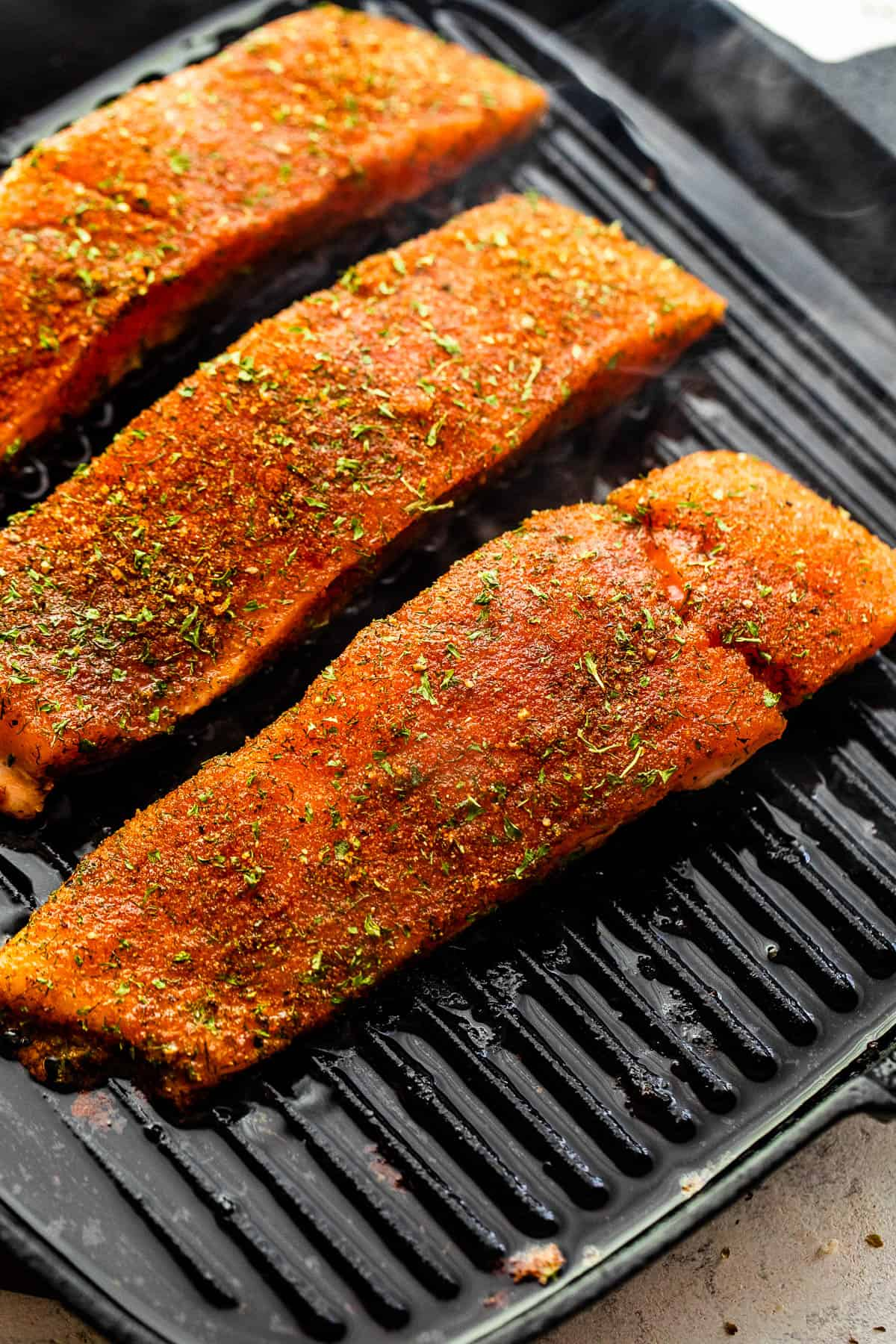 grilling salmon fillets on a black grill pan