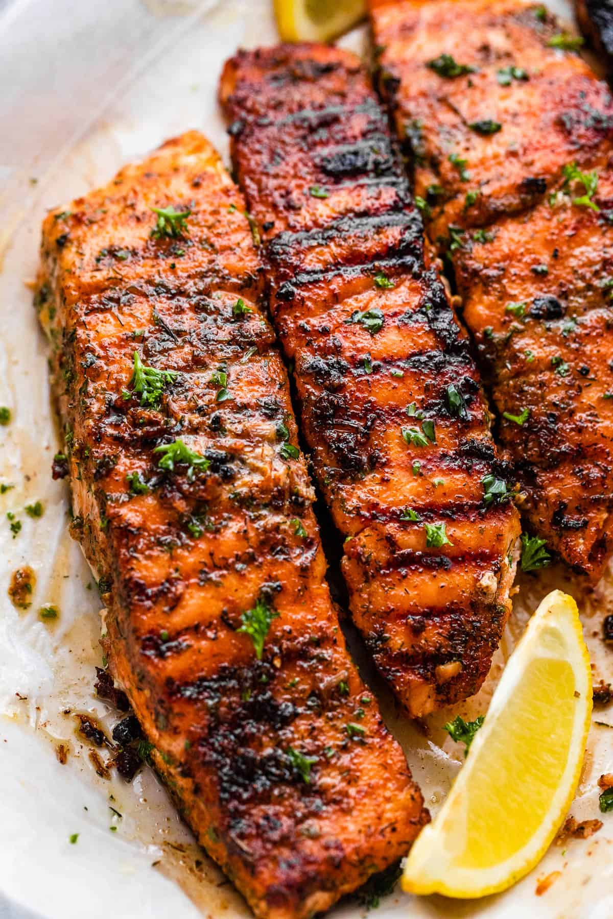 grilled salmon fillets on a plate with lemon wedges