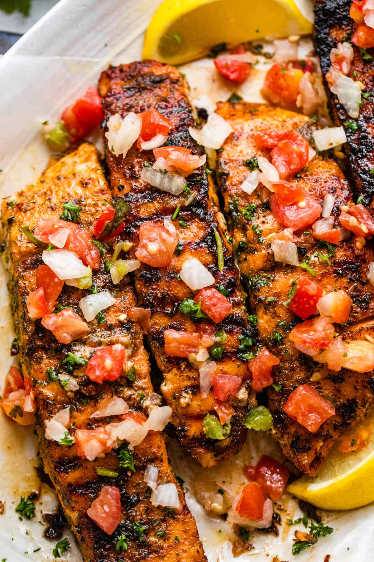 close up photo of three brown sugar grilled salmon fillets topped with pico de gallo