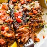 three grilled salmon fillets topped with tomatoes and onions