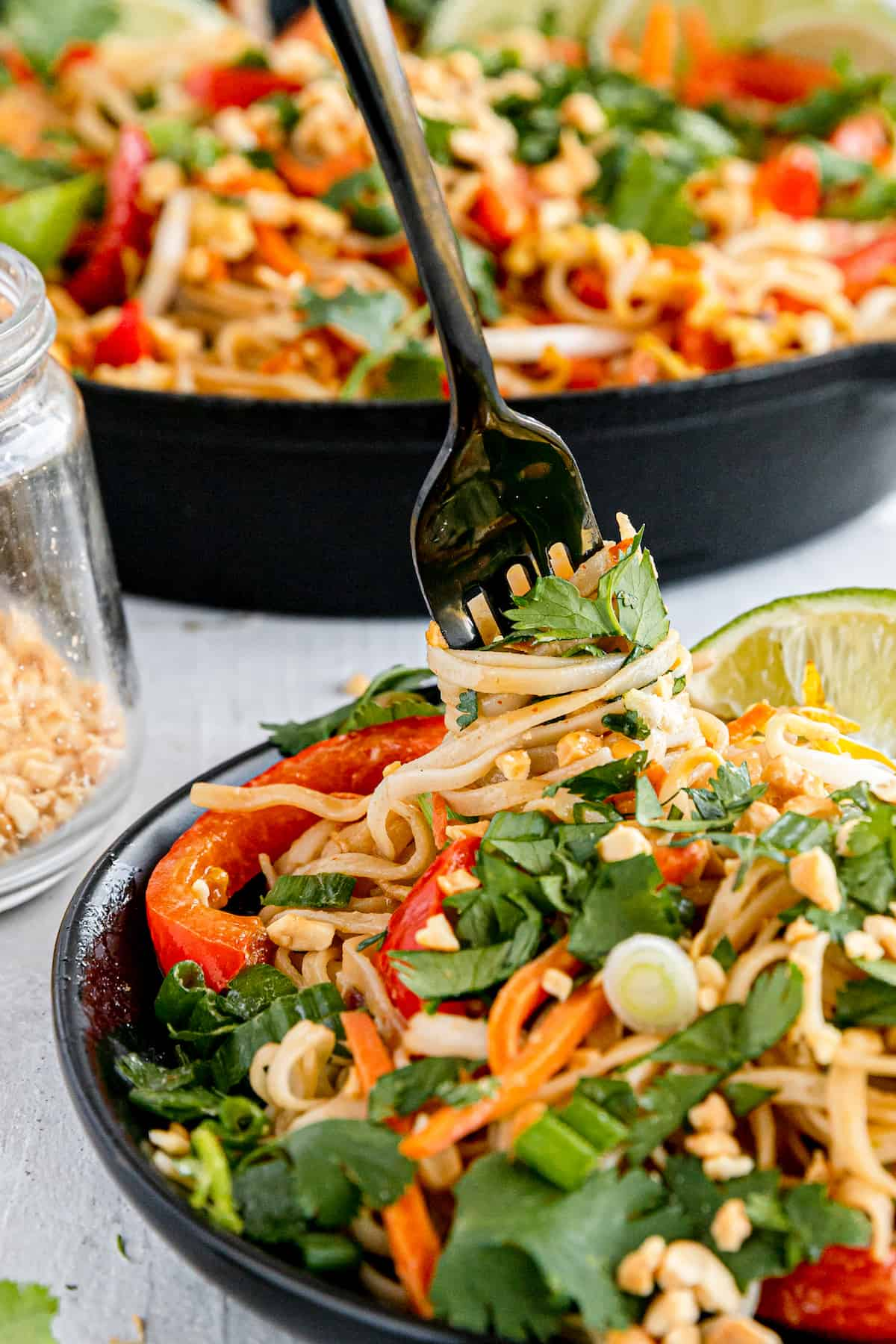 A Close-Up Shot of a Fork Digging Into a Plate of Pad Thai