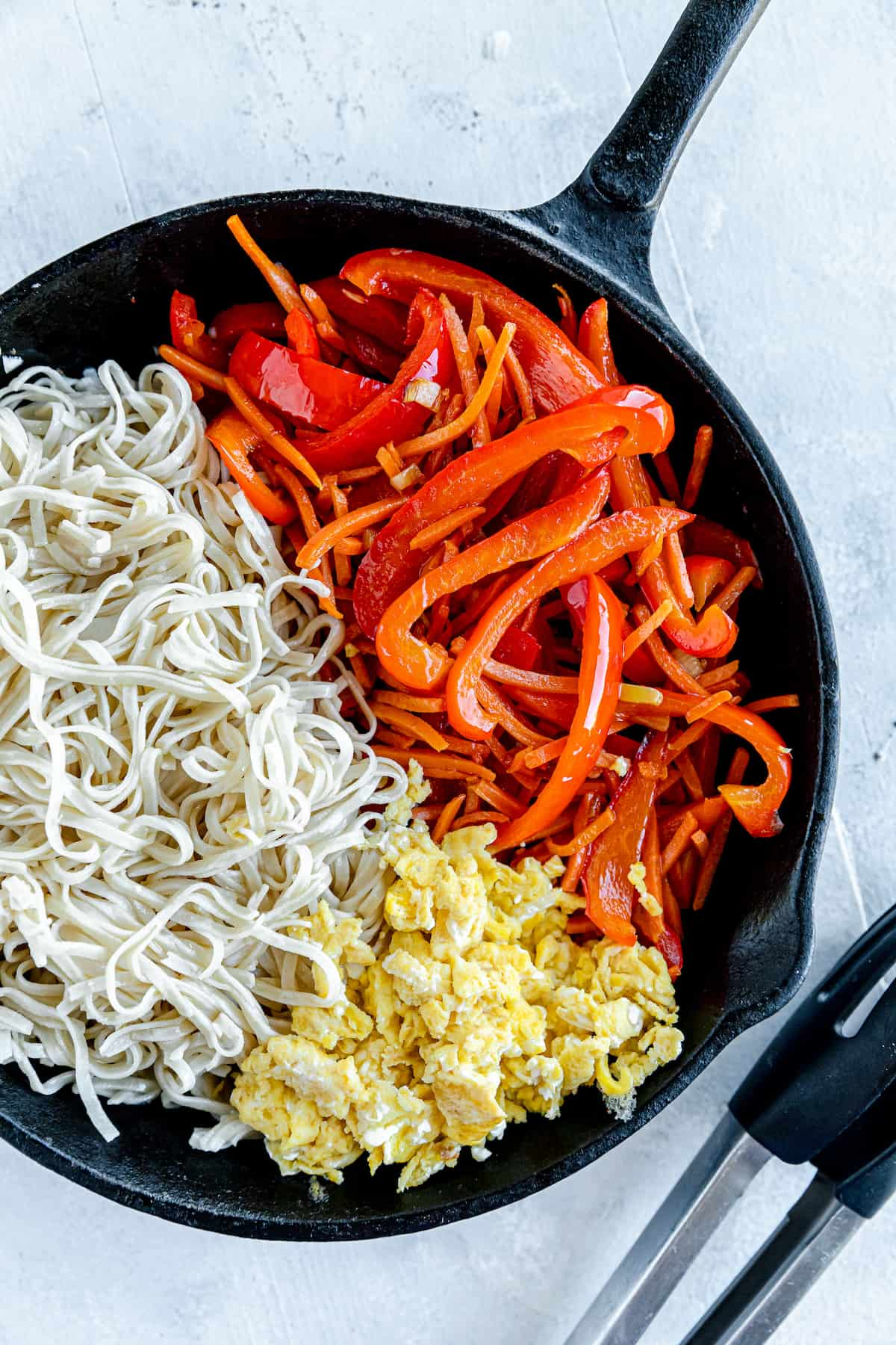 Scrambled Eggs, Brown Rice Noodles and Chopped Veggies Inside of a Black Skillet