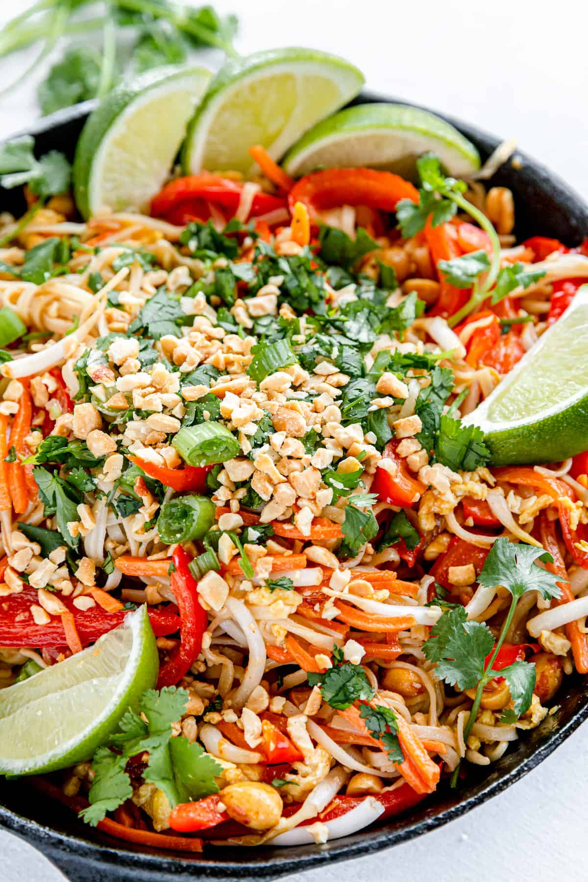 A Pan Filled with Homemade Pad Thai and Garnished with Fresh Lime Wedges