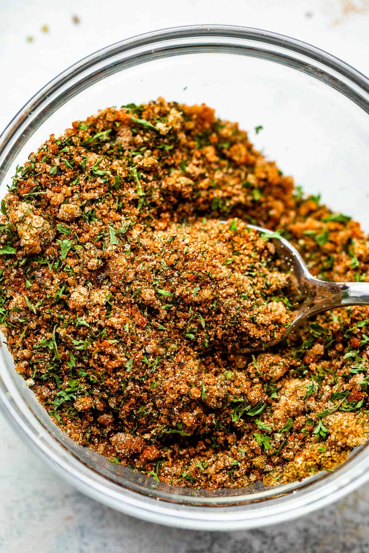 seafood seasoning blend in a small glass mixing bowl with a teaspoon inside