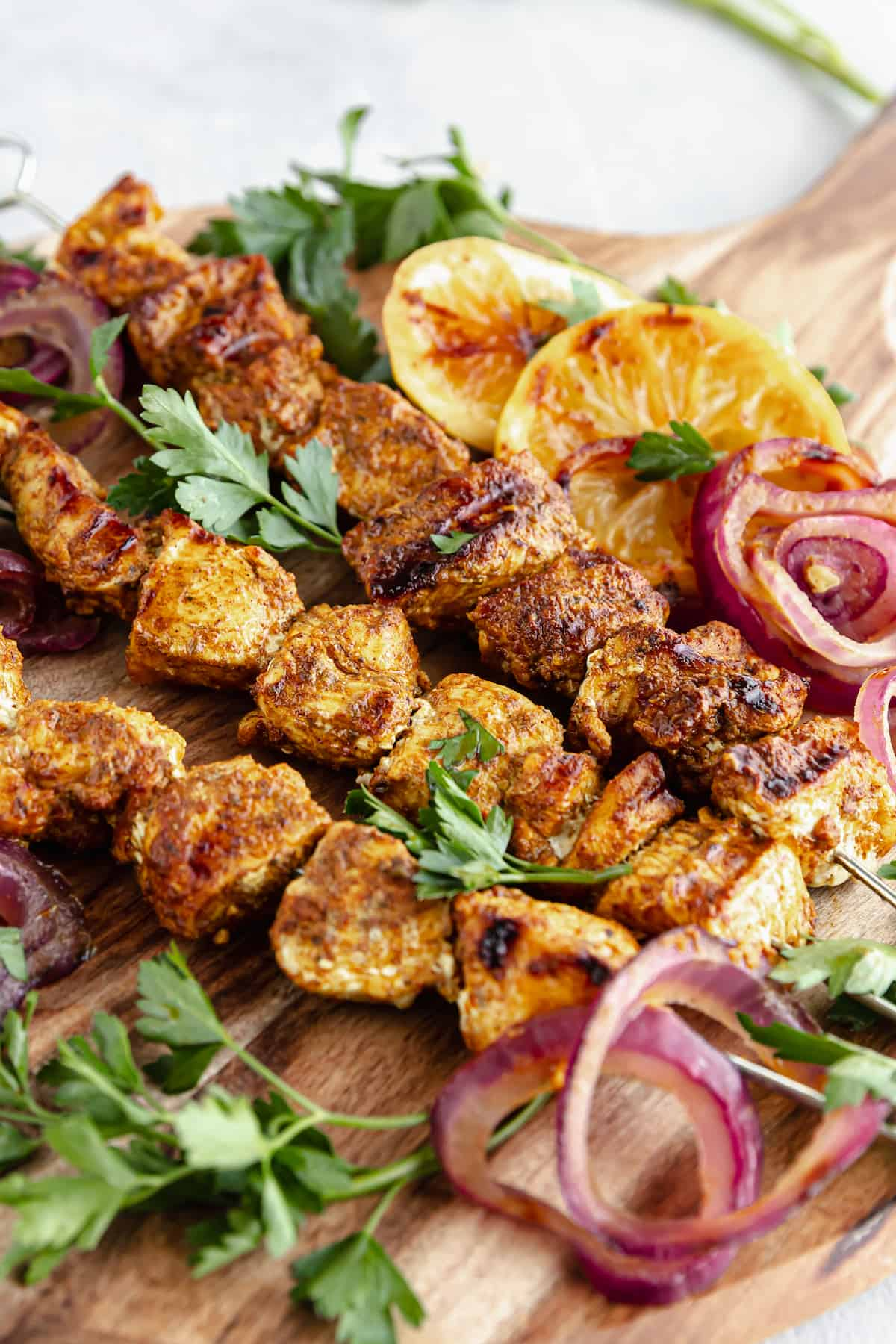 A Cutting Board on a Table Holding Onions, Lemon Slices and Shawarma Grilled Chicken Skewers