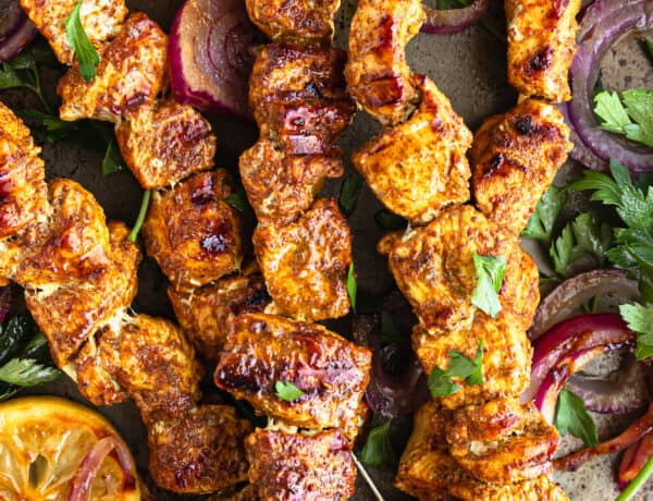 Five Shawarma Grilled Chicken Skewers on a Metal Pan with Onions, Lemon Slices and More
