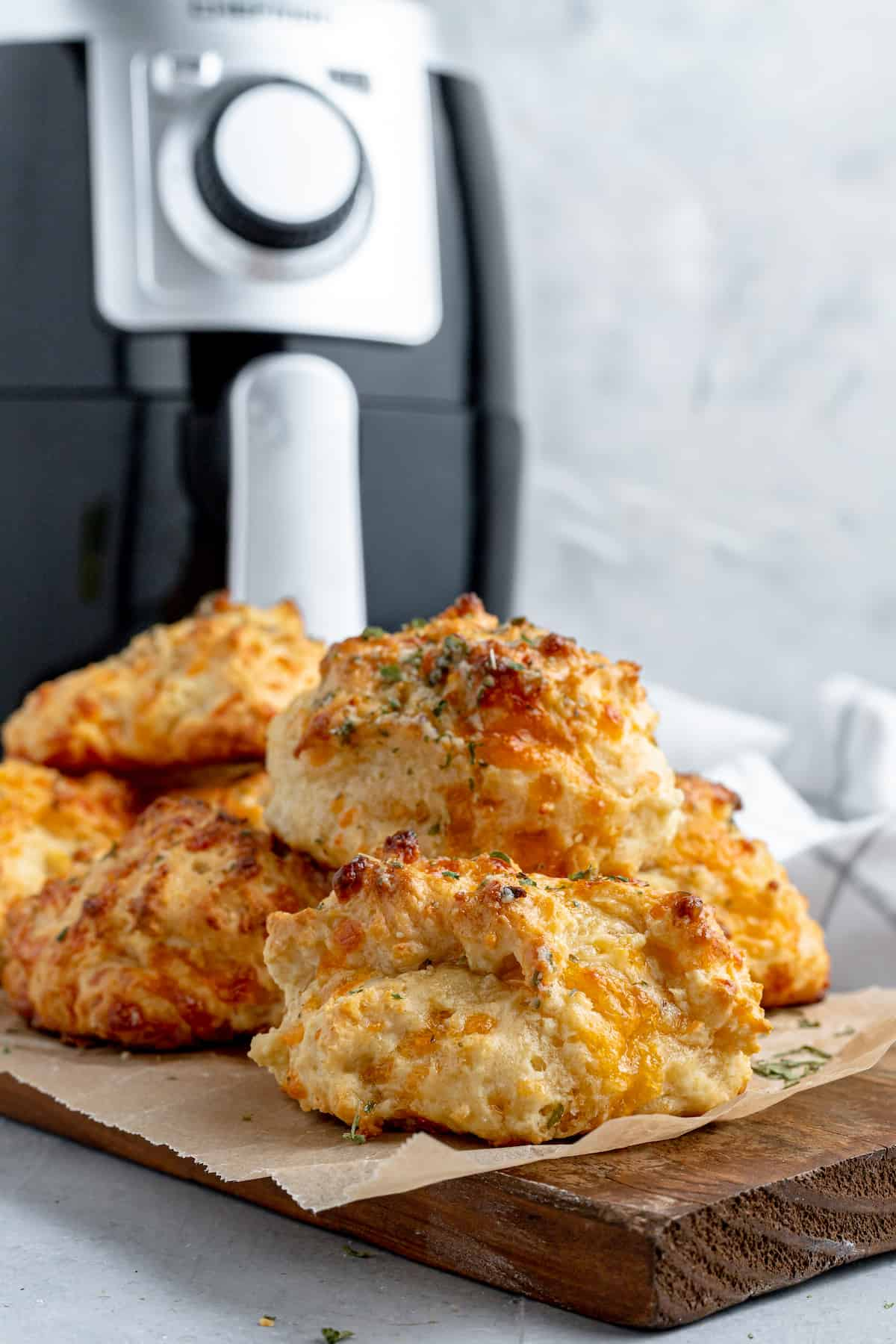 A Pile of Red Lobster Biscuits on a Cutting Board with an Air Fryer in the Background
