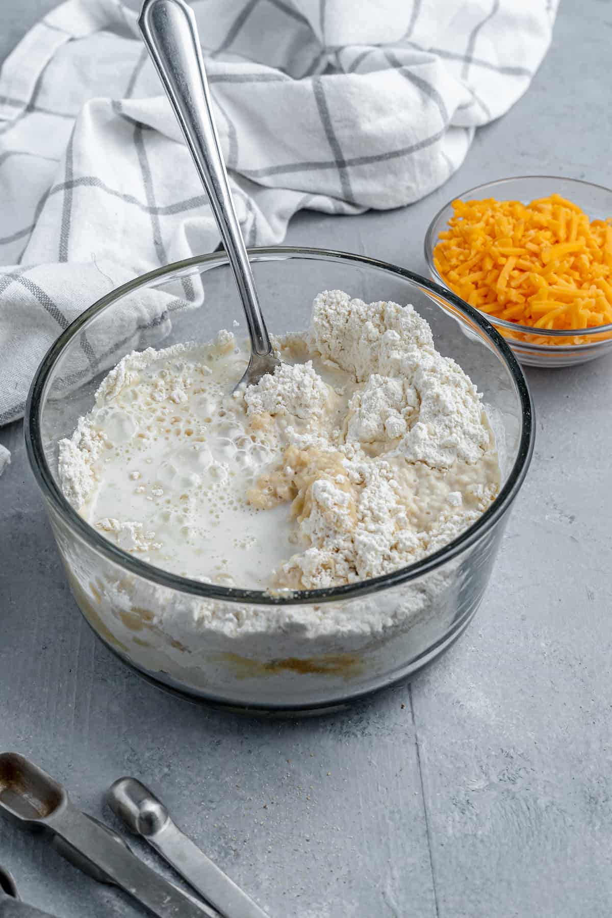 Bisquick Mix, Milk and Butter in a Bowl Beside a Dish of Shredded Cheddar