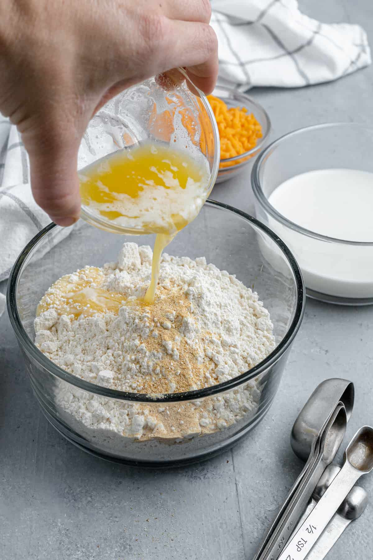 Melted Butter Being Poured Over a Bowl of Bisquick Mix