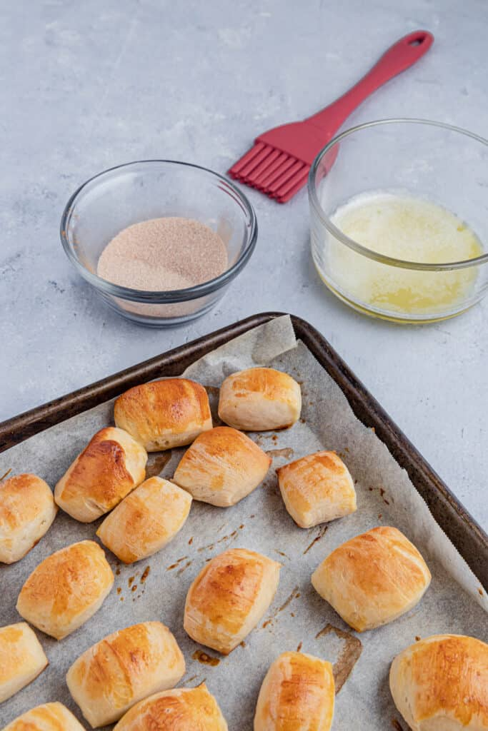 Baked pretzel bites with a bowl of butter and a bowl of cinnamon sugar