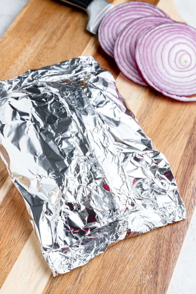 Folded foil on a cutting board and stuffed with cheeseburgers