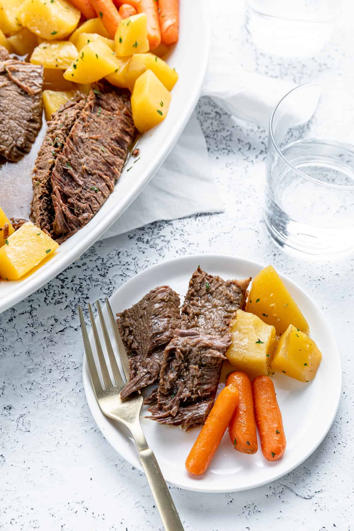 A white plate with pot roast, carrots and potatoes
