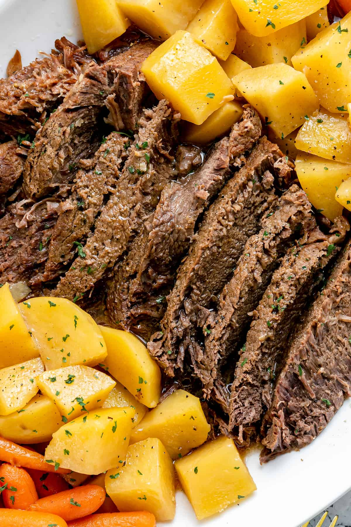 Pot roast with potatoes on a white plate
