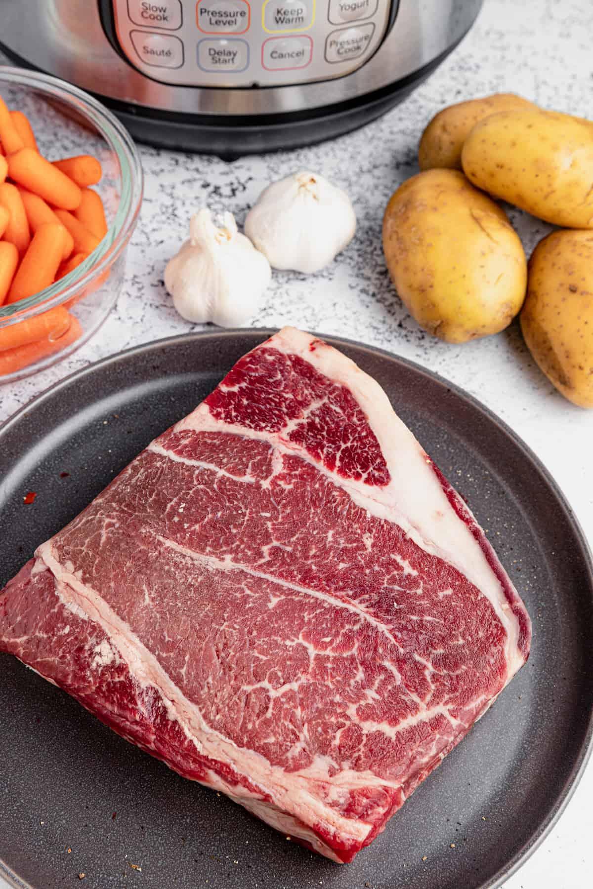 steak, potatoes, garlic and carrots