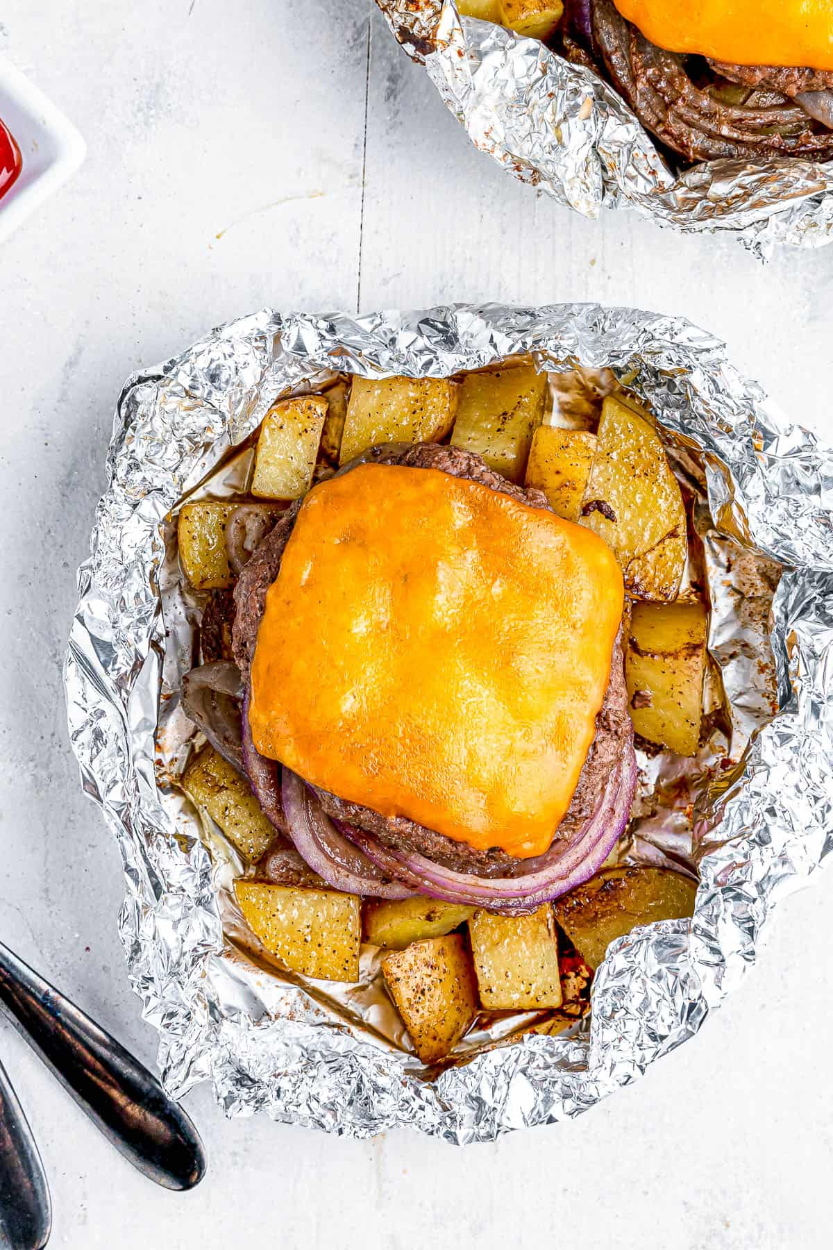 Two cheeseburgers in foil with potatoes