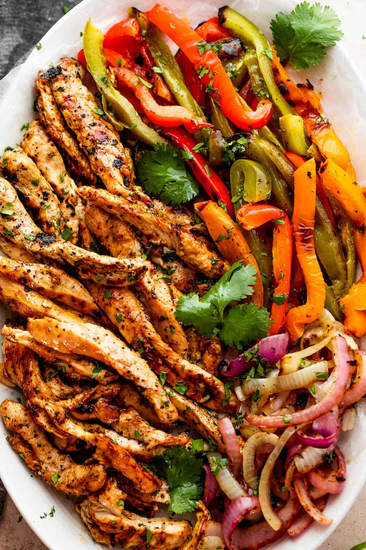 grilled chicken strips, colorful bell pepper strips, and onions on a serving plate garnished with cilantro leaves