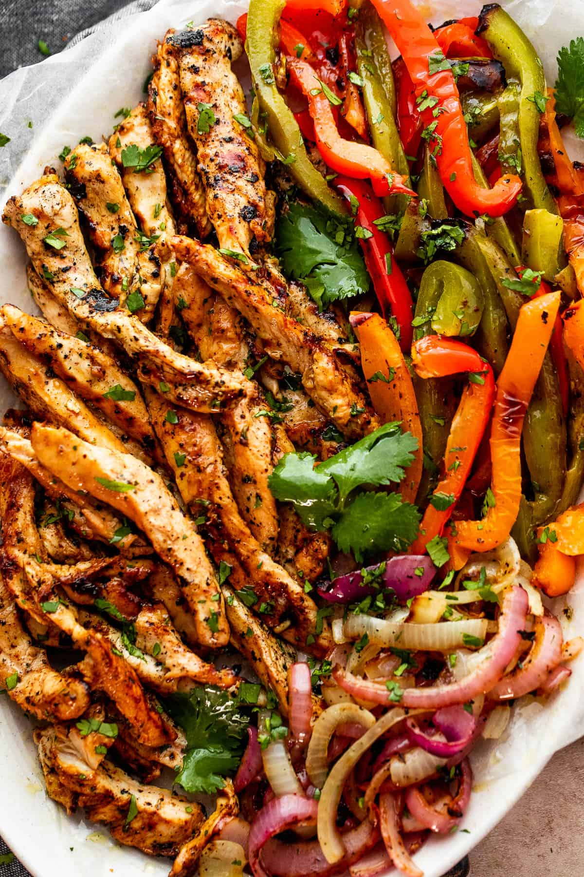 grilled chicken fajitas with chicken strips, colorful bell pepper strips, and onions on a serving plate garnished with cilantro leaves