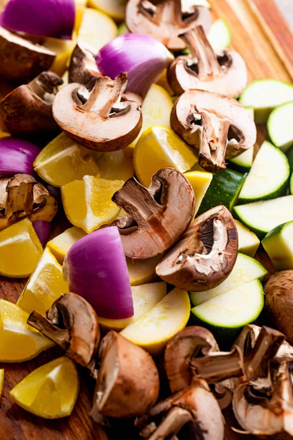 a pile of chopped mushrooms, red onions, lemons, and squash on a wooden board