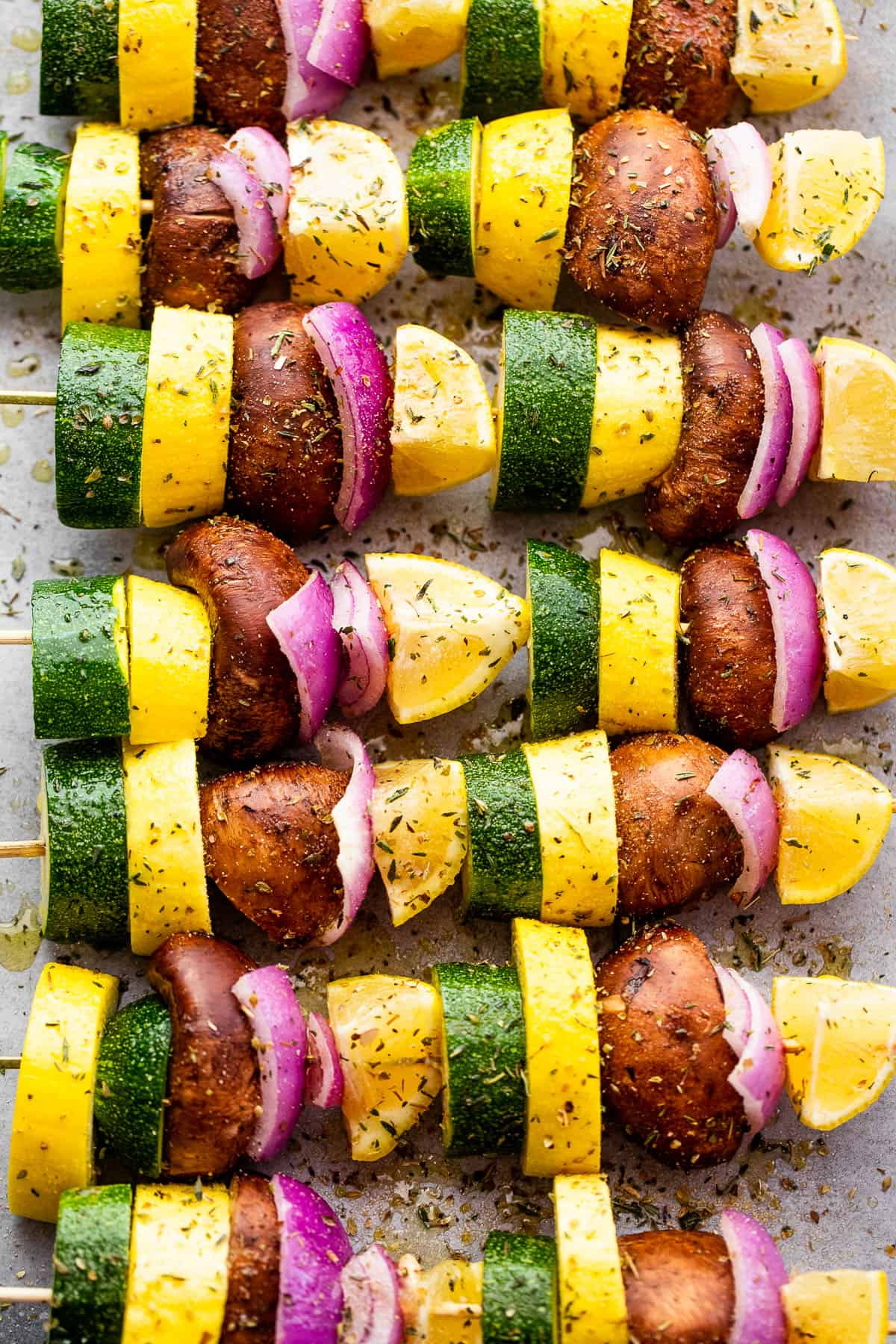 eight squash, red onions, lemons, and mushrooms threaded on wooden skewers