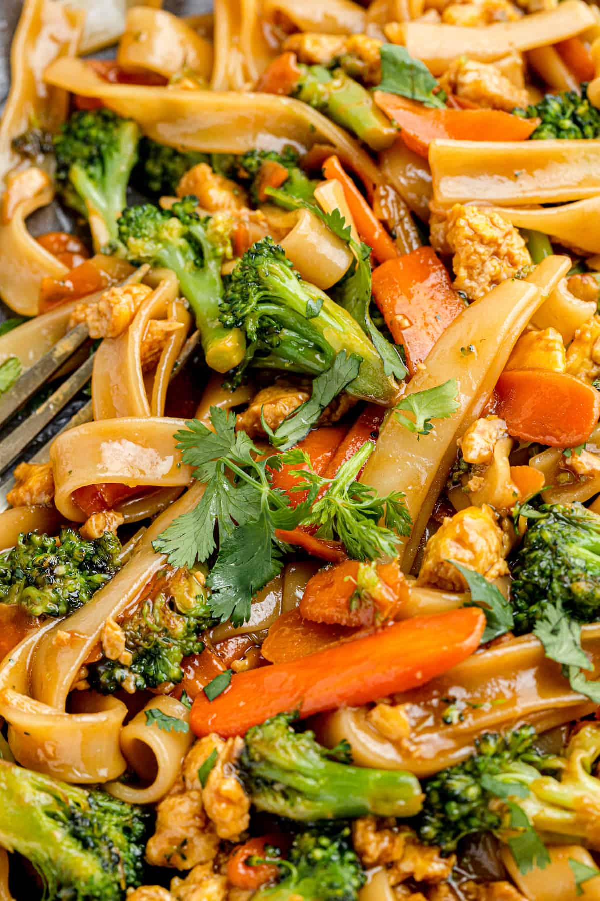 A Super Close-Up Shot of Pad See Ew with a Fork Peeking Through in the Corner
