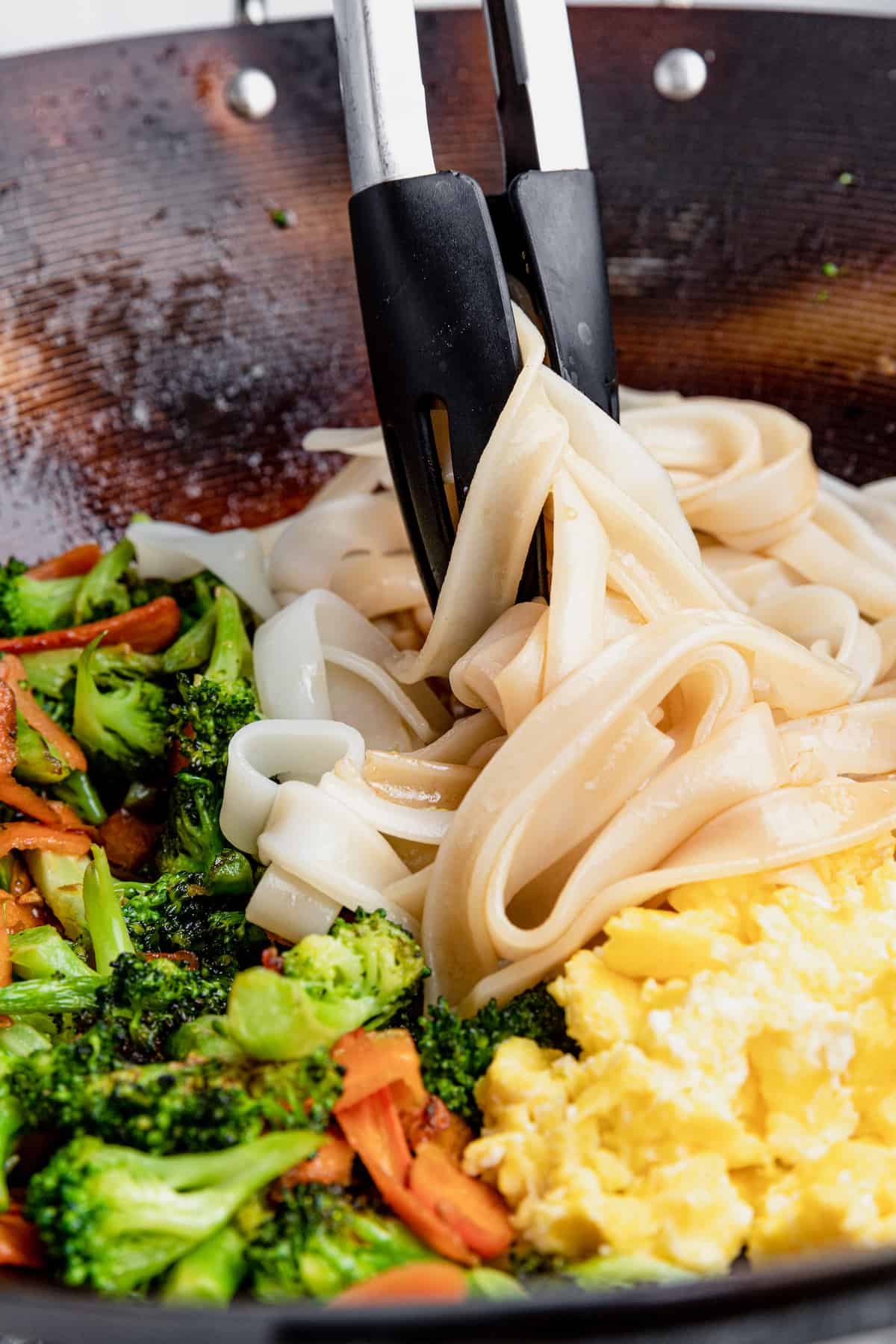 A Pair of Tongs Mixing the Noodles with the Eggs and Vegetables