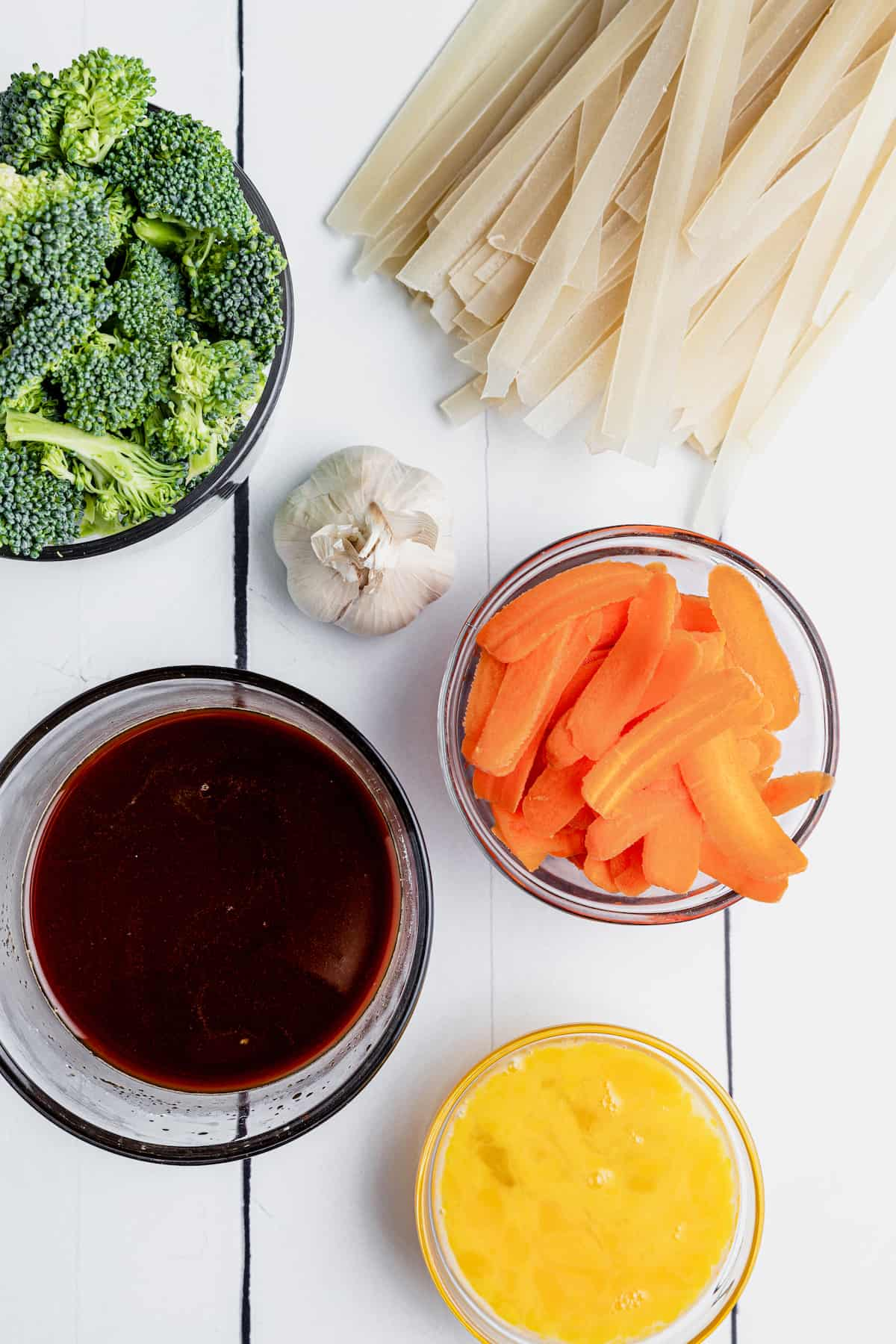 Broccoli, Flat Rice Noodles, Carrot Slices and the Rest of the Ingredients on Top of a White Picnic Table