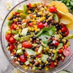 Cowboy caviar with avocado, corn, tomatoes, black-eyed peas, beans and cilantro in a large glass bowl