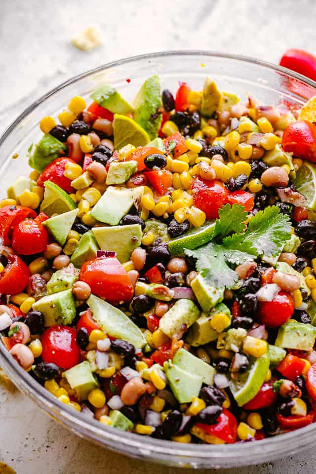 avocado, corn, tomatoes, black-eyed peas, beans and cilantro in a large glass bowl