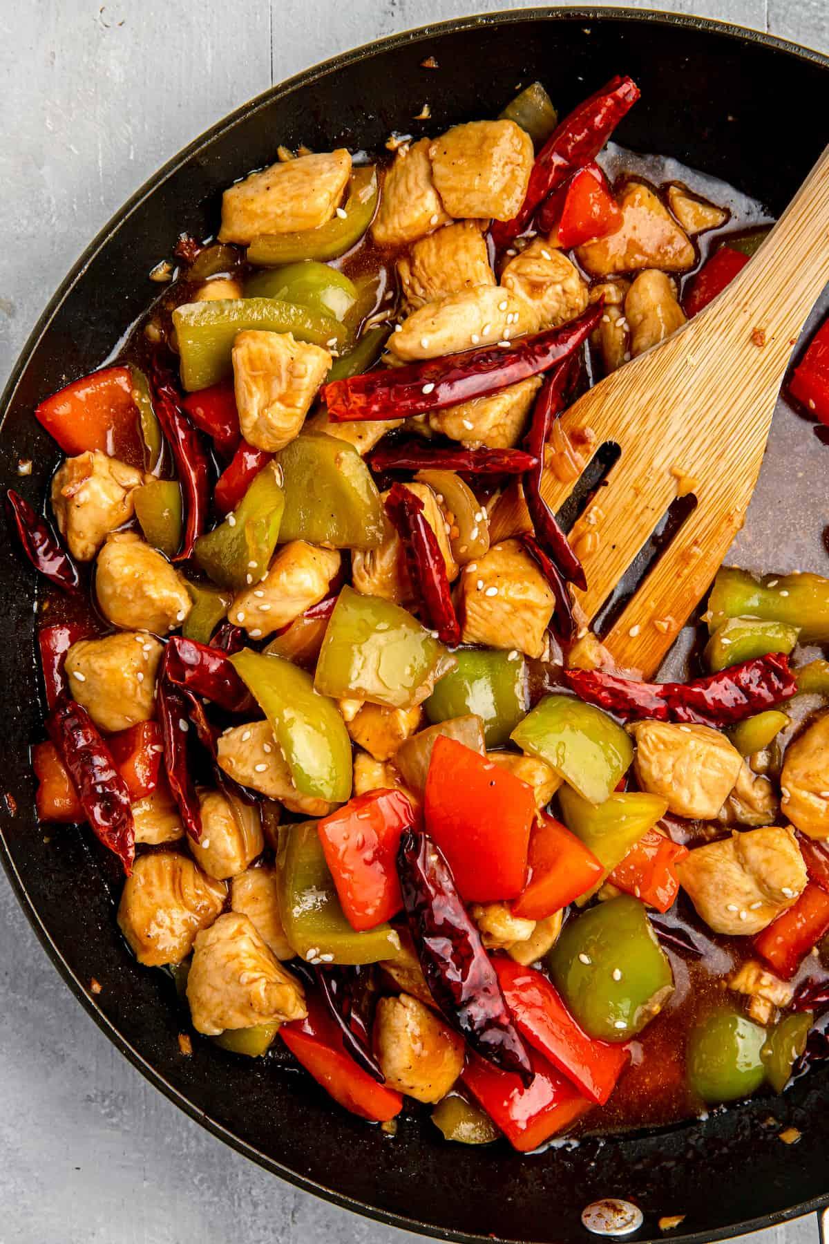 Szechuan chicken stir-fry in a cast-iron skillet with a wooden spatula.