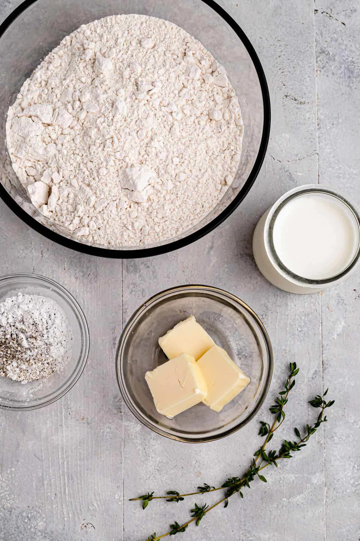 Clockwise from top: all-purpose flour, milk, butter, a sprig of thyme, seasonings and baking powder.
