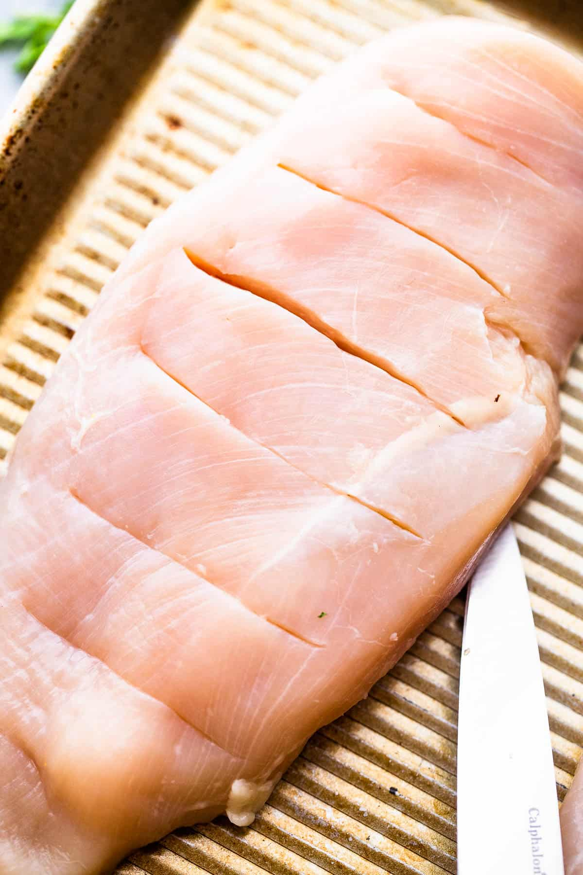 raw chicken breasts cut hasselback style