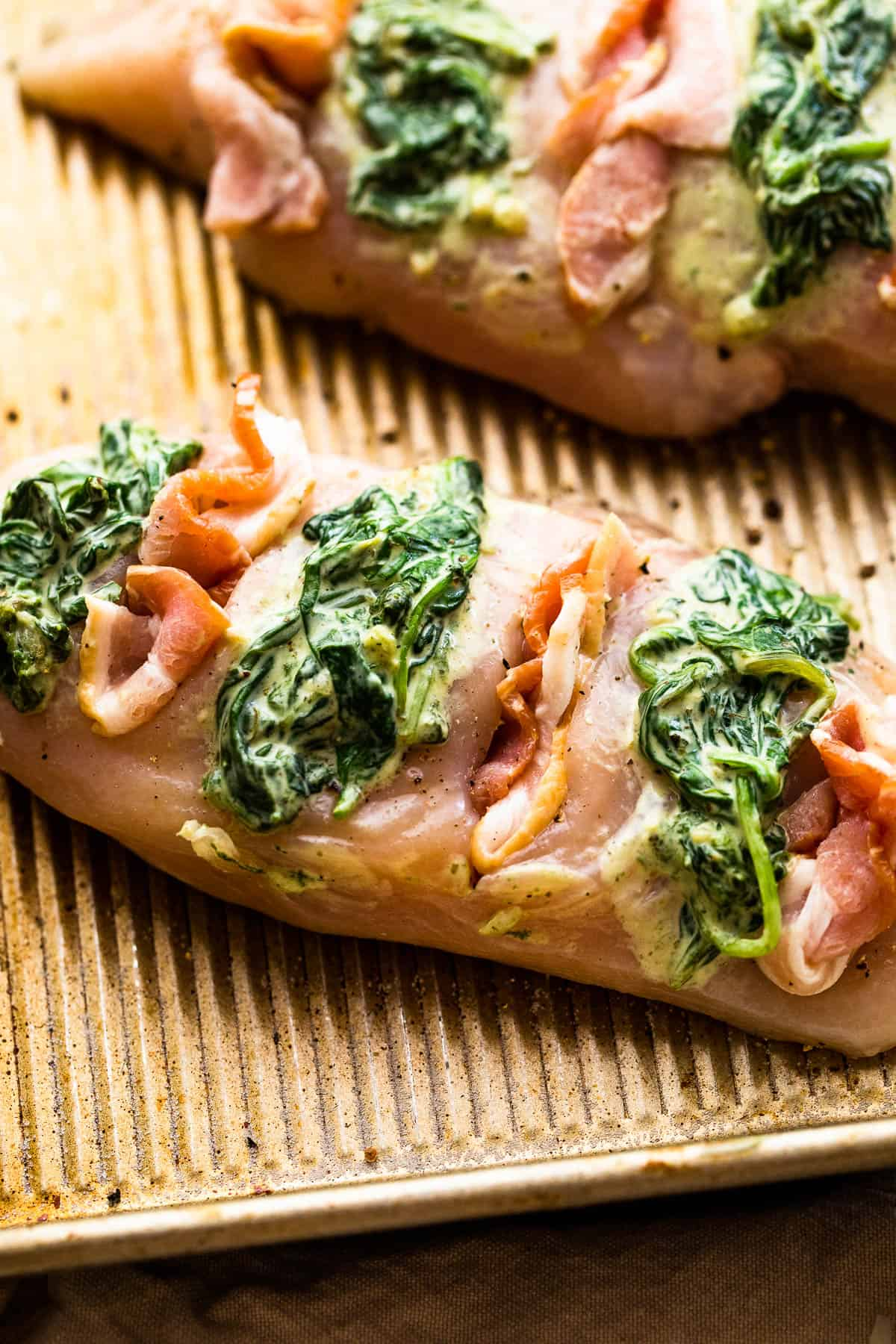 raw chicken breasts cut hasselback style and stuffed with creamed spinach plus bacon
