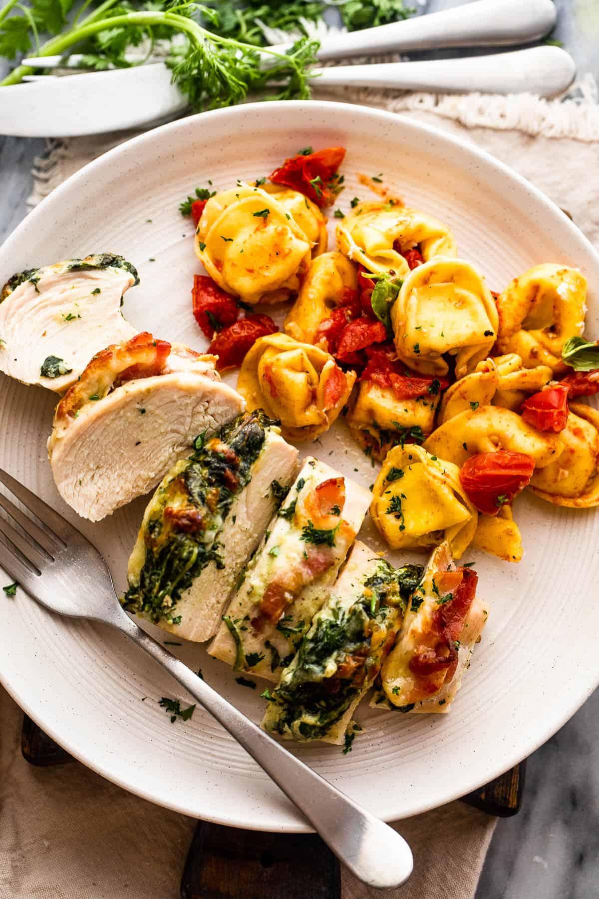 cut up stuffed chicken breast served alongside tortellini pasta
