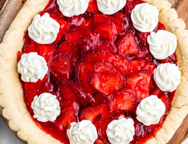 overhead shot of strawberry pie garnished with dollops of cream