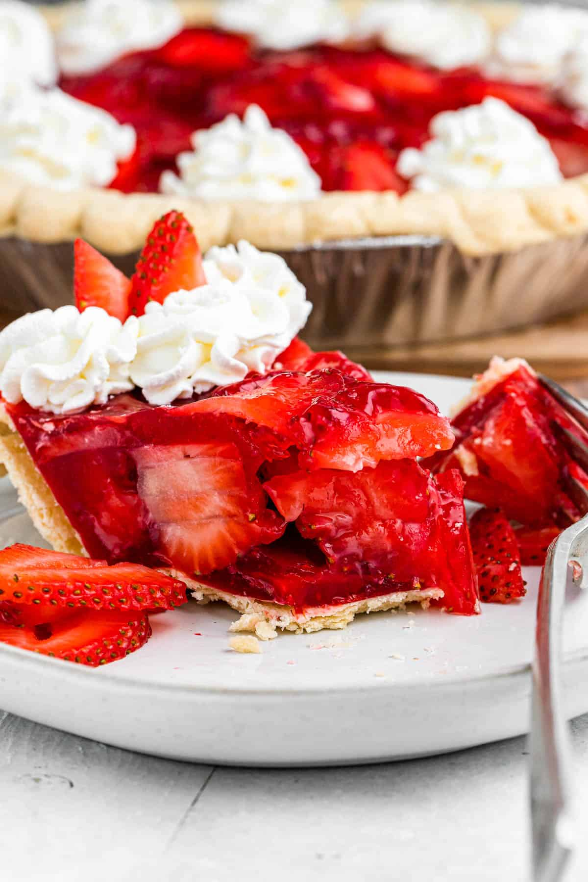 a slice of strawberry pie set on a plate with a fork