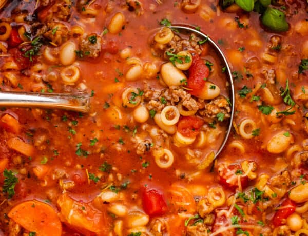pasta fagioli soup in a white dutch oven with ladle inside the soup