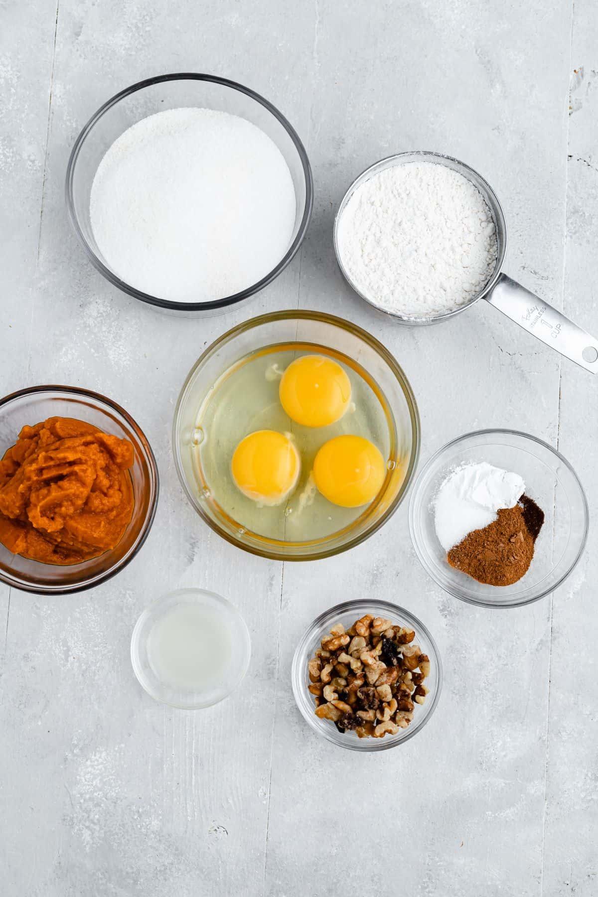 Clockwise from top: flour, spices, walnuts, lemon juice, pumpkin puree, sugar. Center: 3 eggs.