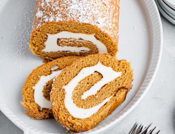A pumpkin roll cake, dusted with powdered sugar, on a platter. Two slices have been cut and lie on the platter as well. Two forks are on the table nearby.