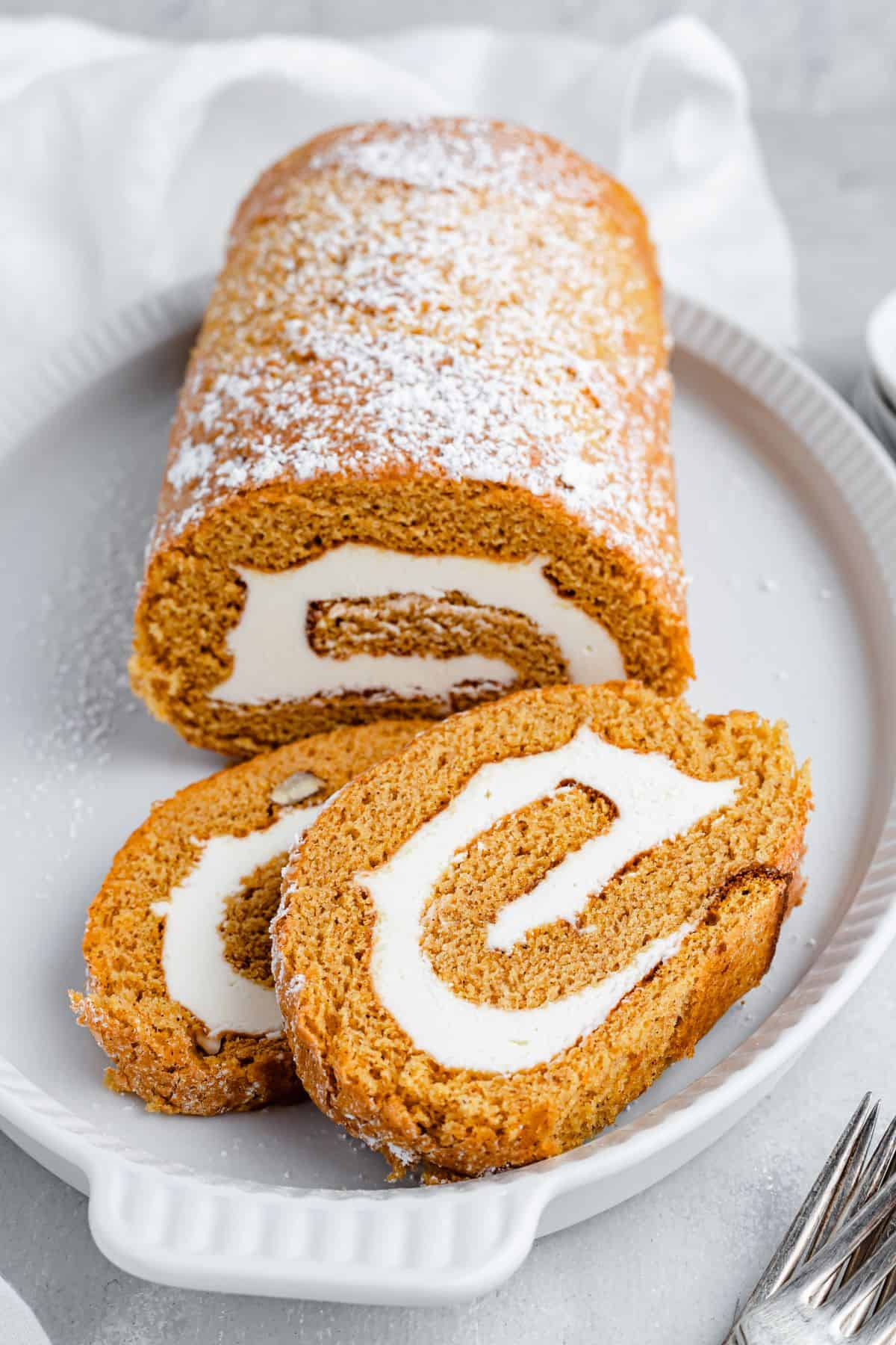 A shot of the pumpkin roll cake, dusted with powdered sugar, with two slices overlapping on a platter.