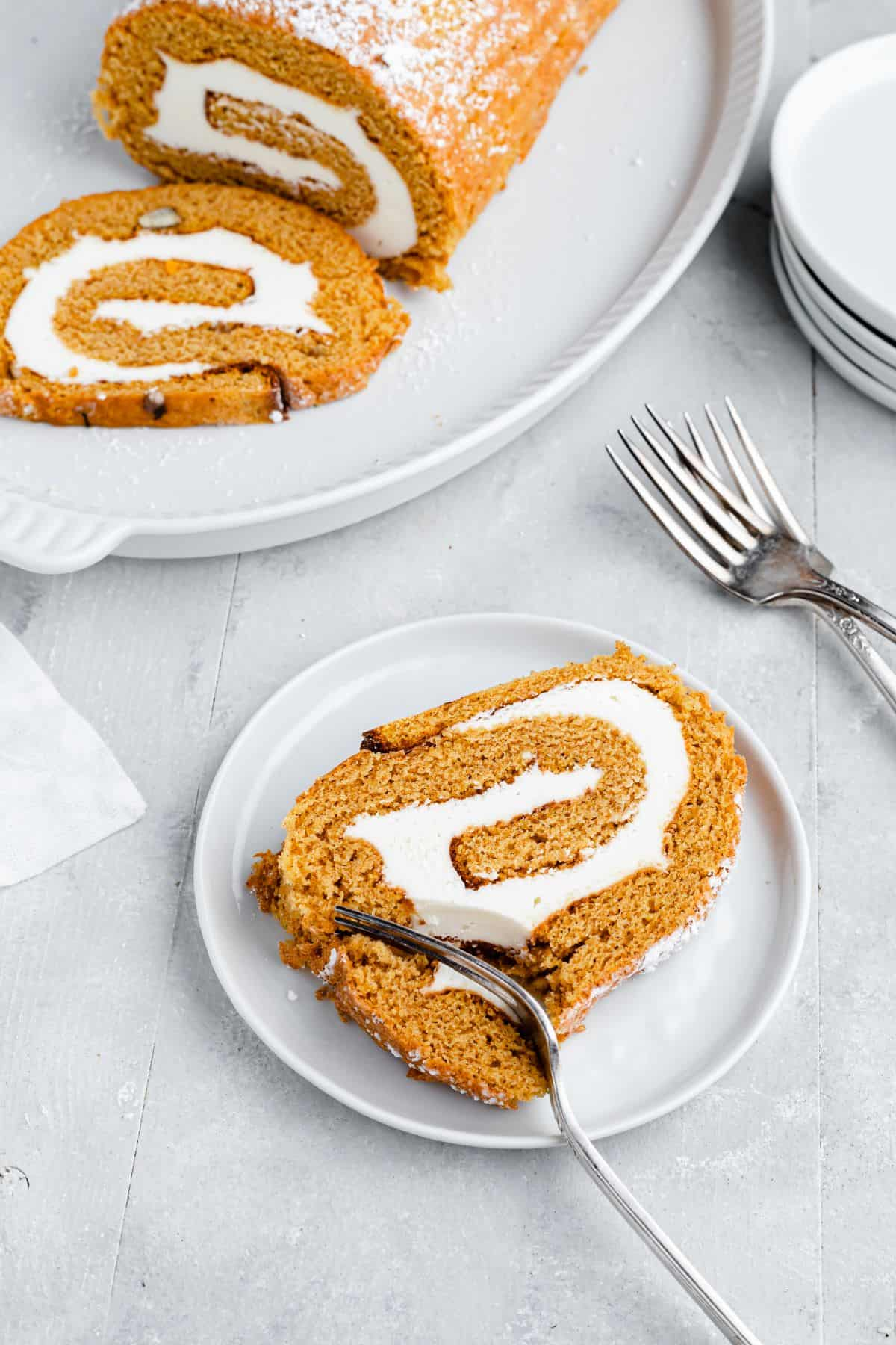 A slice of pumpkin roll cake with a fork cutting into it; in the background, the remaining cake is on a platter with another slice ready to serve.