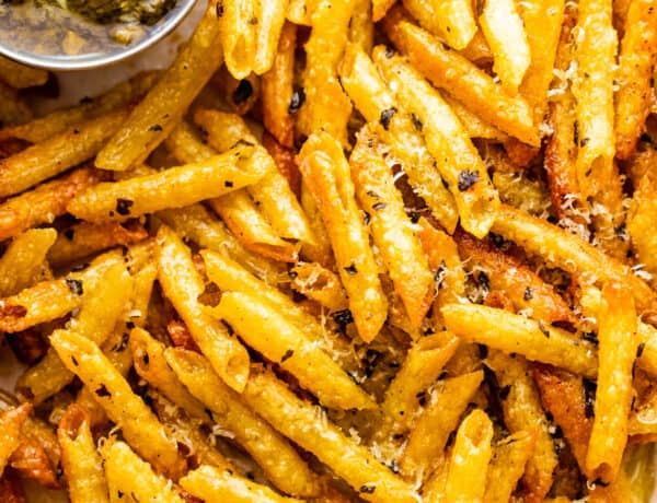 close up of baked pasta chips served with basil pesto