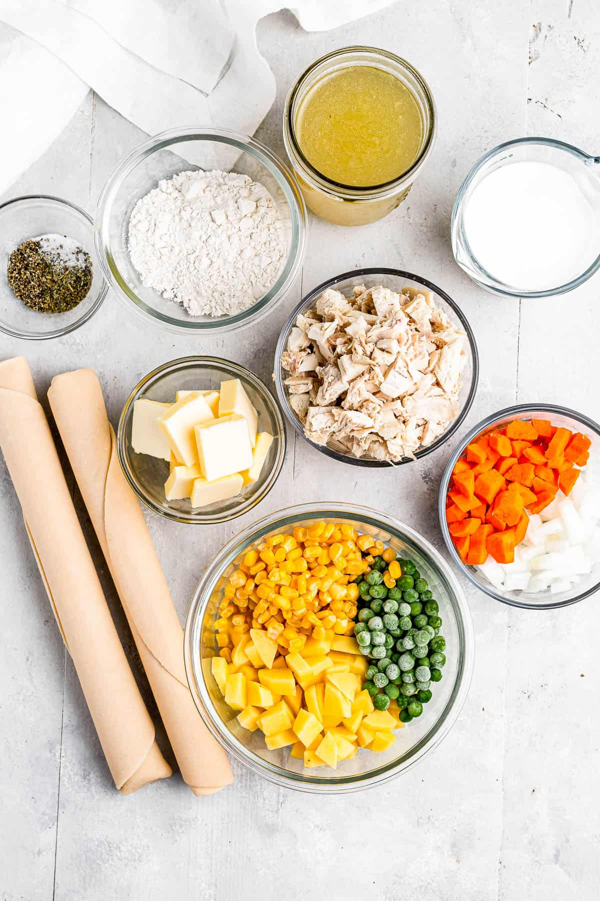 Clockwise from top: chicken broth, milk, chopped carrots and onions, a bowl of peas, corn, and diced potatoes, butter, seasonings, and flour.
