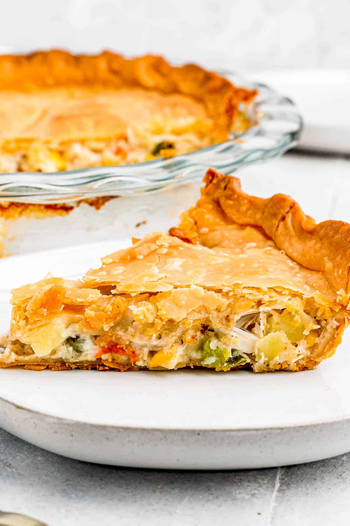 In the background, the baked chicken pot pie. In the foreground, a slice of the pie on a plate with a fork.